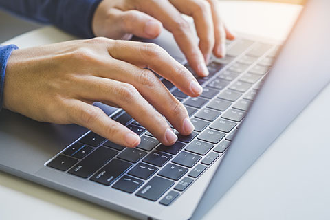 picture of hands typing on a laptop